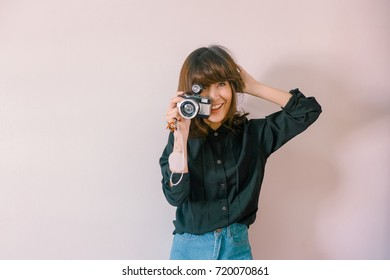 A young hipster woman photographer holding retro film lomo camera  - Soft light vintage filter