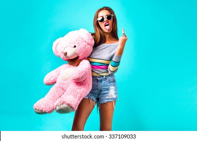 Young hipster woman playing with big fluffy pink toy bear, showing tongue and middle finger, wearing sexy mini shorts and sunglasses, cheeky emotions, yo, cool, crazy.
