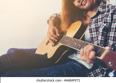Young hipster woman playing a guitar.