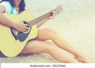 Young hipster woman playing guitar on the beach