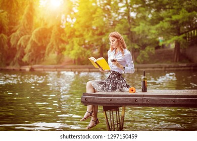 Young hipster woman relaxing on dock in park reading book drinking glass of red wine - Modern lifestyle and freedom concept with millennial girl enjoying day in park - Warm sunshine color filter tone
