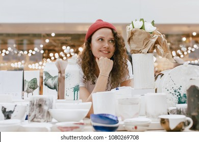 Young hipster woman selling behind counter with her ceramics and porcelain hand-painted at local market of craftsmen, small business