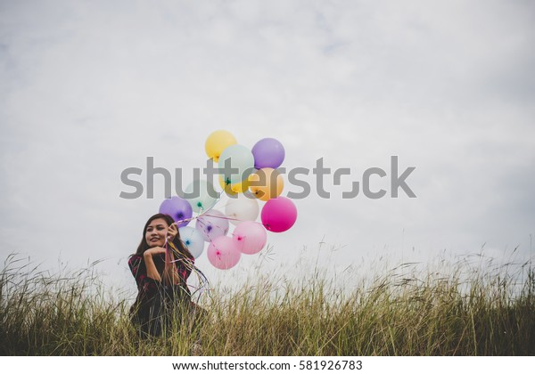 Young hipster woman sitting holding colorful balloons in field, blue sky background.