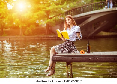 Young hipster woman sitting on dock in park with book holding glass drinking wine  - Modern lifestyle and freedom concept with millennial girl enjoying day in park - Warm sunshine color filter tone