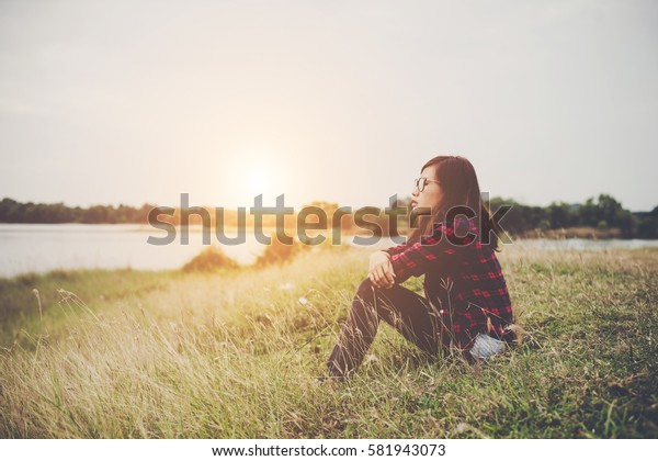 Young hipster woman sitting on grass near the lake relaxing enjoy with fresh air.