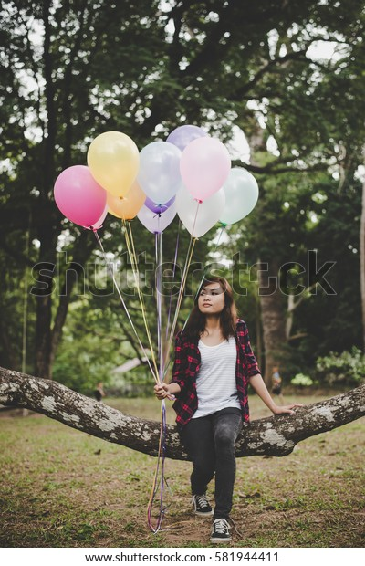 Young hipster woman sitting on tree branch with colorful of balloons in hand, Relaxing enjoy holiday.