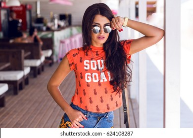 Young hipster woman in stylish sunglasses, swag urban style, bright orange print t-shirt. She is posing in beach bar, enjoying  summer day .