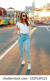 Young hipster woman in stylish T-shirt in trendy sunglasses in blue jeans in sneakers posing in an amusement park on the background of a bright orange summer sunset. Pretty girl enjoying the weekend.