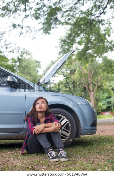 Young hipster woman waiting for roadside assistance after her car breaks down at the side of the road sitting against her car.