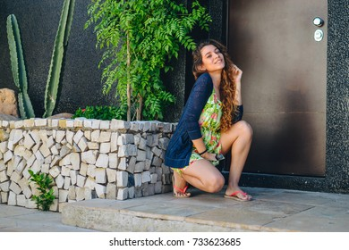 Young hipster woman, wearing trendy clothers, dress and coat, making a modern pose for the photo