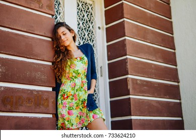 Young hipster woman, wearing trendy clothers, dress and coat,  leaning against a wooden wall, closed eye