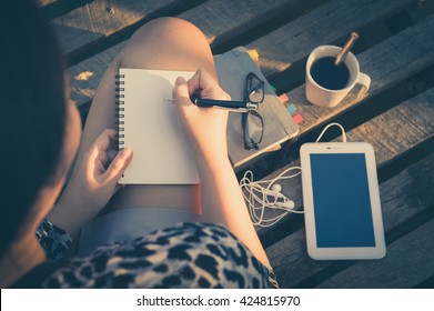 Young hipster woman writing journal on small notebook while sitting on wood bridge in morning time on weekend with high contrast sun lighting and vintage filter effect