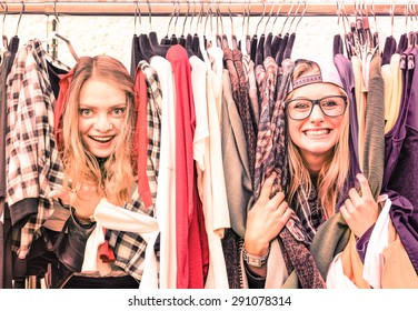 Young hipster women at clothes flea market - Best friends sharing fun time shopping in the city - Happy girlfriends enjoying happy life moments - Soft focus on warm vintage pink marsala filtered look