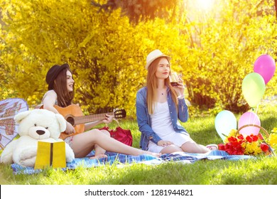 Young hipster women having fun together at picnic at sunset - Best friends women friendship concept with young girls couple drinking wine playing guitar - Warm sunshine color