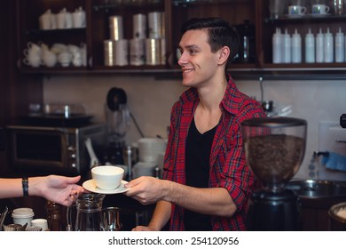 Young hipster working in cafe. Barista is passing an order to a customer smiling