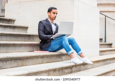 Young Hispanic American college student studying in New York, wearing black blazer, blue jeans, sneakers, earphone, sitting on stairs of office building, listening music, working on laptop computer.