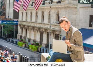 Young Hispanic American College Student traveling, studying in New York City, with hair bun, wearing glasses, brown patterned jacket, blue jeans, sitting on Wall Street, working on laptop computer.
