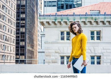 Young Hispanic American College Student Studying in New York City, with brown curly hair, wearing glasses, yellow long sleeve T shirt, blue jeans, holding laptop computer, standing outside on campus.