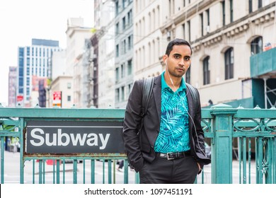 Young Hispanic American Man traveling in New York, wearing black jacket, patterned polo shirt, white earphone, shoulder carrying back bag, listening music, standing on street by Subway sign, waiting.