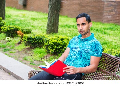 Young Hispanic American Man wearing green patterned Polo shirt, black pants, white wired earphone, sitting on bench at street park in New York, reading red book, listening music, looking up, thinking.