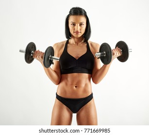 Young hispanic athletic woman working out with dumbbells on white background