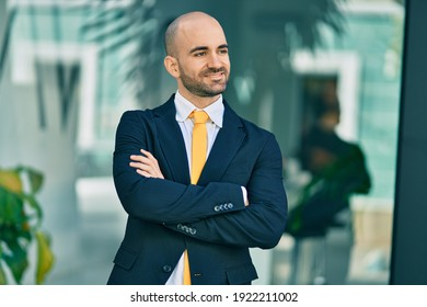 Young hispanic bald businessman with arms crossed smiling happy at the city.