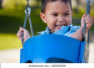 Young hispanic boy with a cute smile that is looking away while riding and holding on to a playground swing.