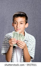 Young hispanic boy with dollar bills in hand and dreamy gaze