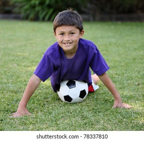 Young Hispanic boy with soccer ball on grass