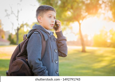 Young Hispanic Boy Walking Outdoors With Backpack Talking on Cell Phone.