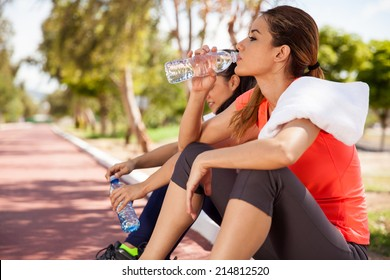 Young Hispanic brunette and her friend drinking water from a bottle after their workout