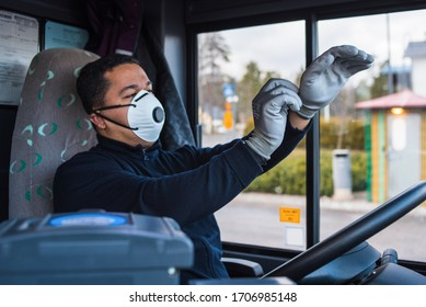 young hispanic bus driver with mask puts protecting gloves on his hand in bus to protect himself from the coronavirus epidemic. covid 19. protect from corona virus. quarantine 2020. stay home.