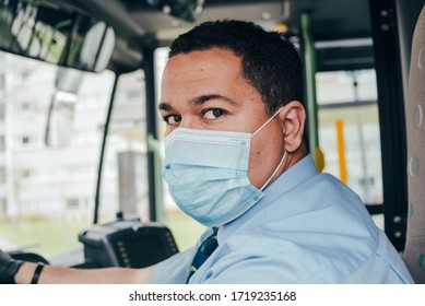 young hispanic bus driver wears blue mask in bus to protect himself from the coronavirus epidemic is alone in bus. covid 19. protect from corona virus. quarantine 2020. stay home.