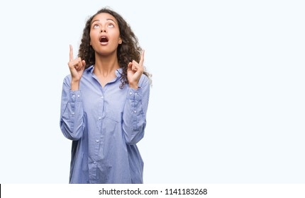 Young hispanic business woman amazed and surprised looking up and pointing with fingers and raised arms.