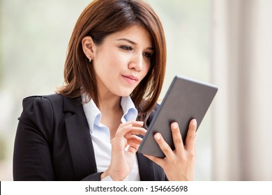 Young Hispanic business woman using a tablet to check her emails