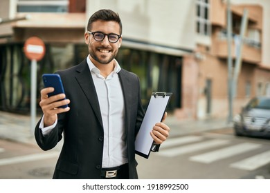 Young hispanic businessman smiling happy using smartphone at the city.