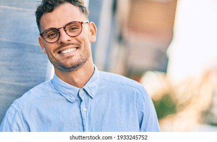 Young hispanic businessman smiling happy standing at the city.