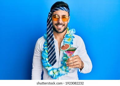 Young hispanic businessman wearing party funny style drinking cocktail looking positive and happy standing and smiling with a confident smile showing teeth