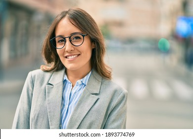 Young hispanic businesswoman smiling happy standing at the city.