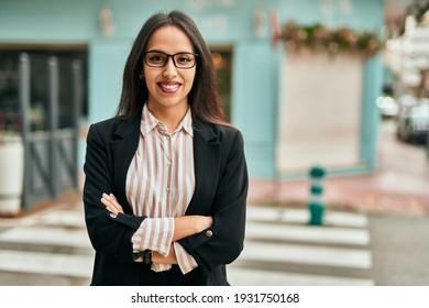 Young hispanic businesswoman smiling happy with arms crossed at the city.