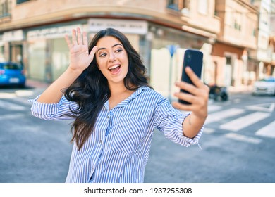 Young hispanic businesswoman smiling happy doing video call using smartphone at the city.
