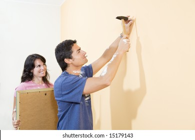 Young Hispanic couple hanging picture on wall