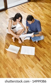 Young Hispanic couple looking at blueprints of new home, high angle view