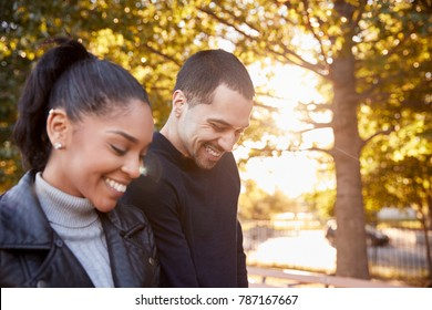 Young Hispanic couple walking in Brooklyn park, close up