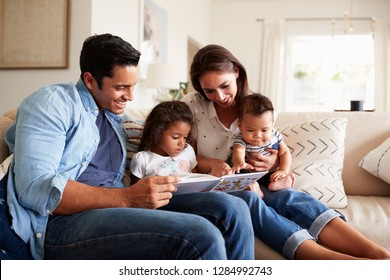 Young Hispanic family of four sitting on the sofa reading a book together in their living room