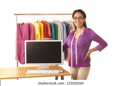 Young Hispanic fashion designer standing at work table with computer