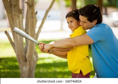 Young Hispanic father and his kid practicing a bat swing and spending time together at a park