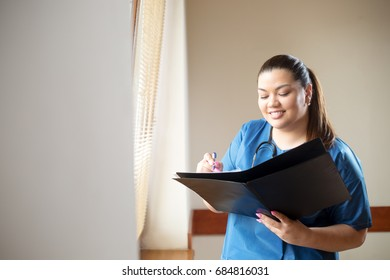 Young hispanic female doctor smiling, holding a report and looking into folder she is holding in her hands