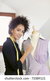 Young hispanic female dressmaker adjusting clothes on tailoring mannequin and smiling at camera. Vertical shape, side view, waist up