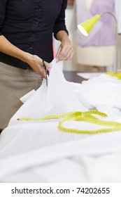 Young hispanic female dressmaker cutting white fabric for bridal gown. Vertical shape, front view, selective focus, copy space